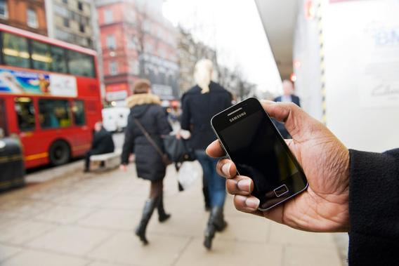 A man uses a Samsung Galaxy Ace smartphone on the streets of London, February 11, 2011.