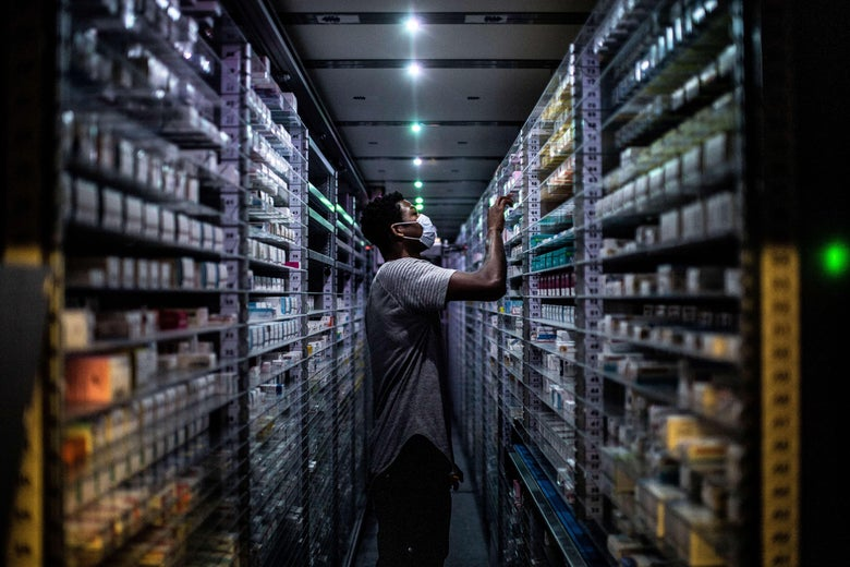 An employee wearing a mask stocks shelves of medicine in a pharmacy
