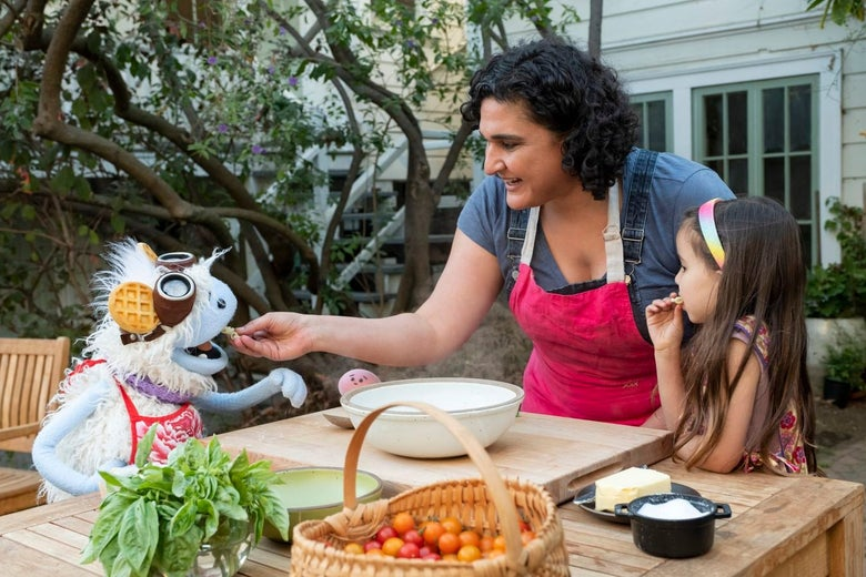 Nosrat feeds Waffles the puppet at an outdoor table as Mochi and a human child look on