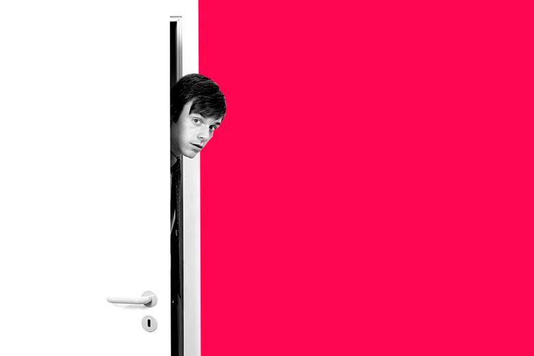 Man peeking his head in from behind a door.