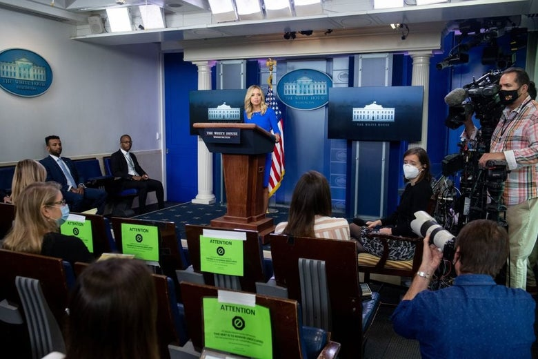 McEnany stands at the White House briefing room lectern in front of two rows of socially distanced reporters and camera operators and photographers wearing masks.