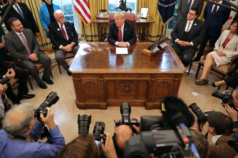 President Trump talking to reporters and surrounded by cameras in the Oval Office in the White House.