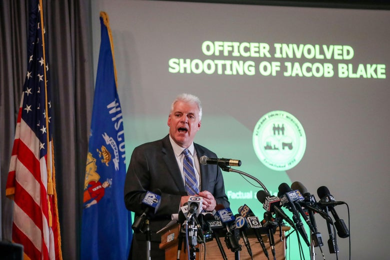"Kenosha District Attorney Michael Graveley speaks at a mic in front of a screen that reads ""Officer Involved Shooting of Jacob Blake"""