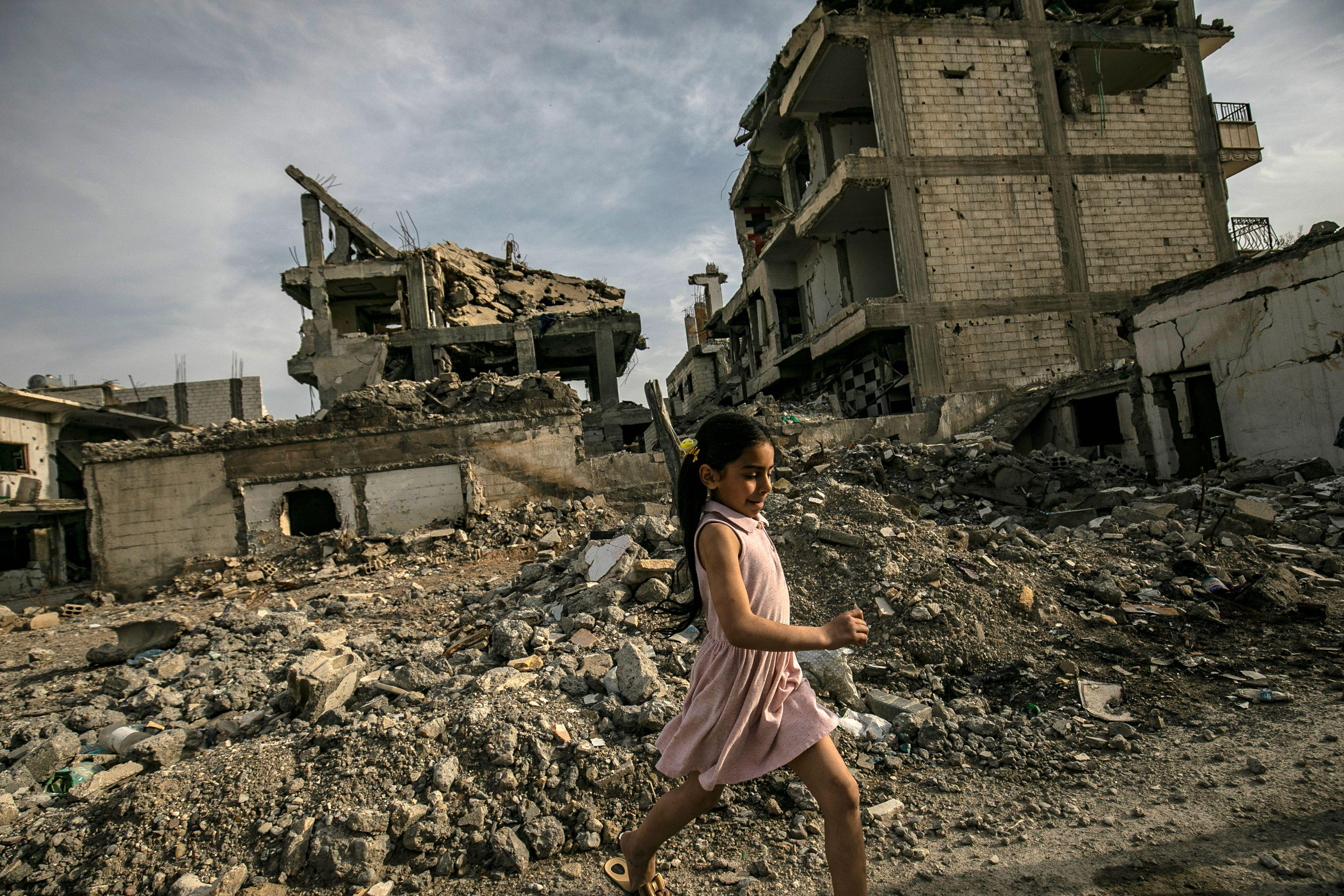 A girl in a pink dress walks in front of rubble and destroyed buildings.