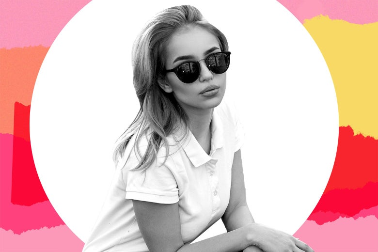 A young blonde woman crouched down in a polo shirt and sunglasses.