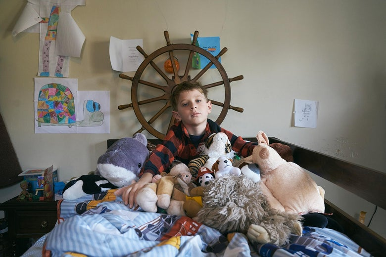 Colin, surrounded by his stuffed animals sitting on his bed.