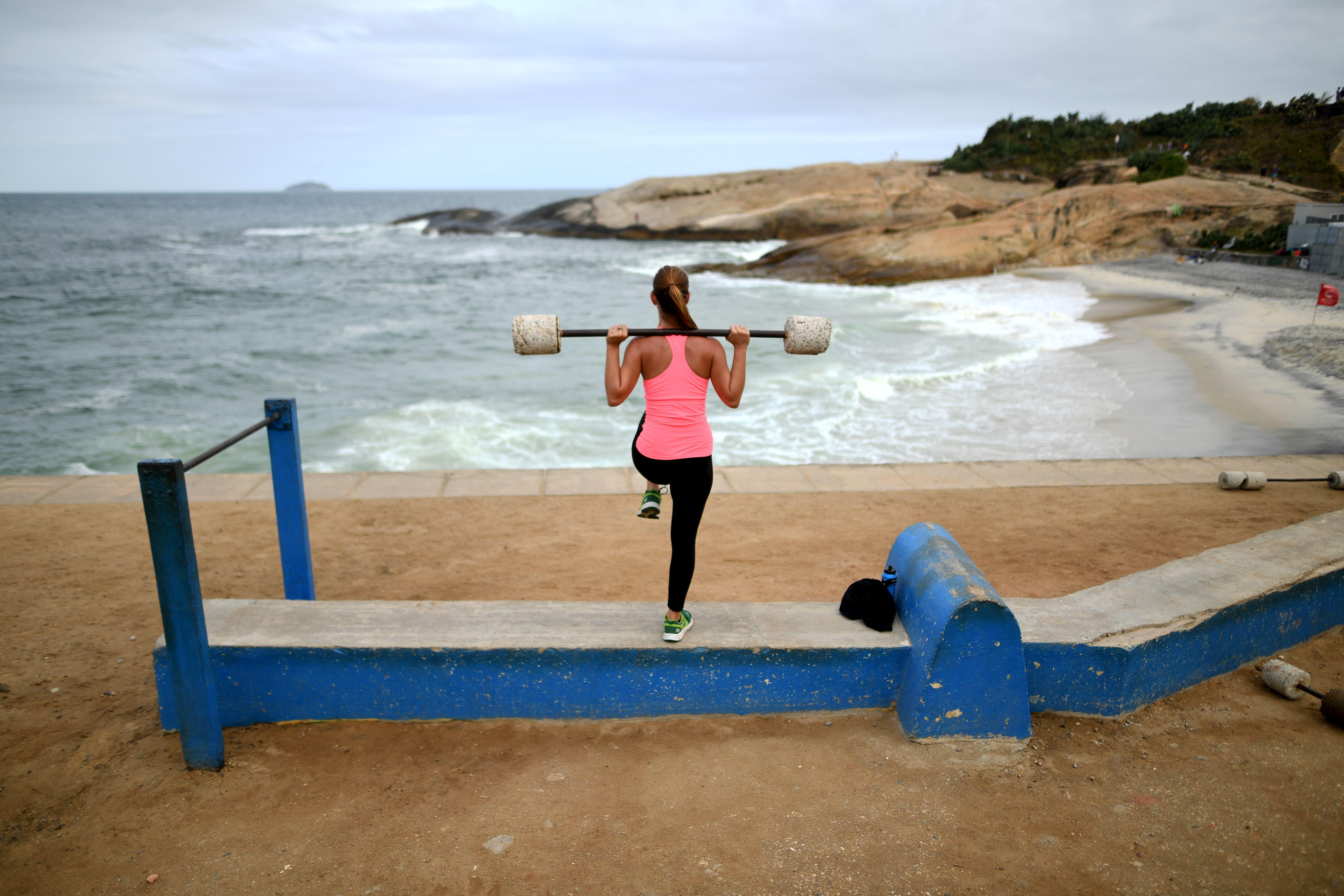A woman lifts weights as she exercises at an outdoor improvised gym close to Ipanema beach in Rio de Janeiro on August 3, 2016.