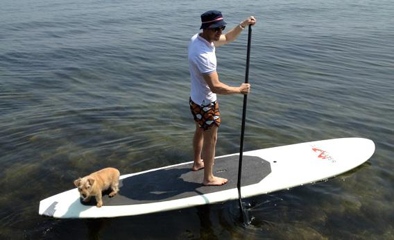 Simon Doonan paddling a paddle board, the trend of the future.
