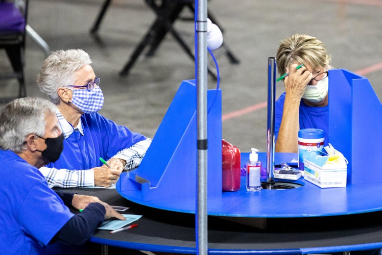 A woman leans her head into her hand in apparent frustration as she sits in front of a blue Lazy Susan on a table. Two other older people sit at the table.