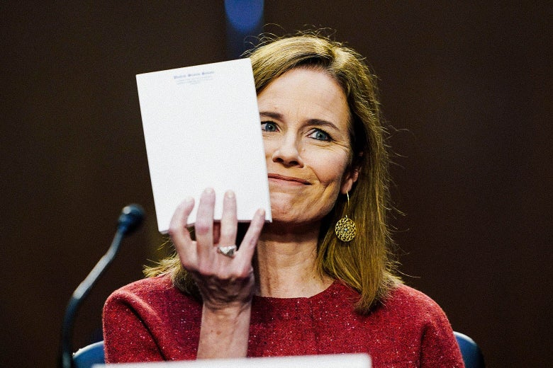 A white woman in a red sweater holds up a blank notepad and smirks.