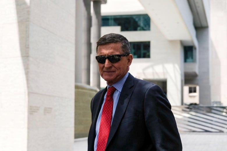 Flynn wearing sunglasses, standing outside a courthouse