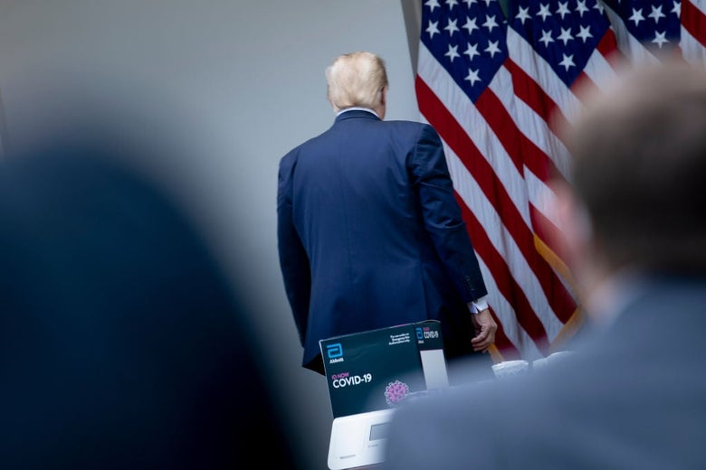 Trump's back is seen in focus from between the blurry shapes of two individuals watching him leave.