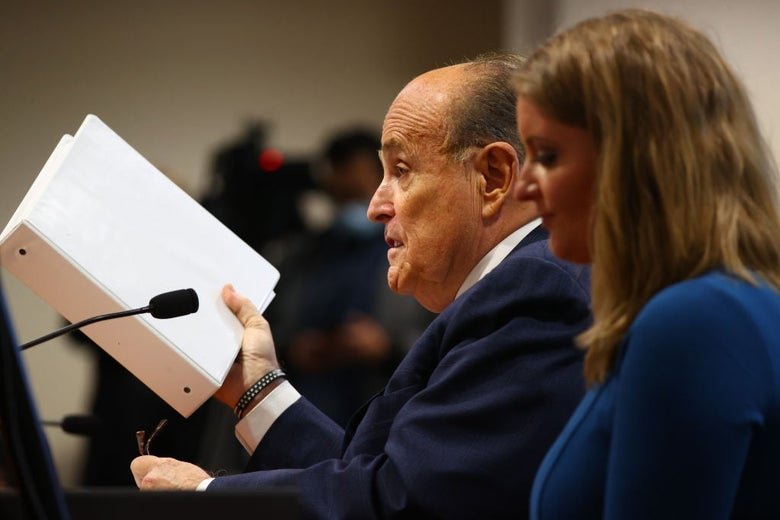 Rudy Giuliani and Jenna Ellis, shot from the side, sit next to each other at a hearing while Giuliani, who is speaking, holds up a white binder.