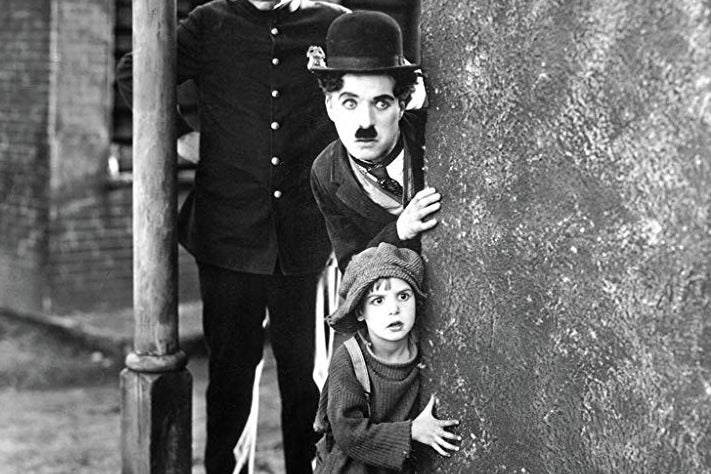 Charlie Chaplin as The Tramp and a child peer around a corner.