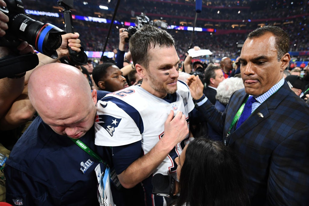 Brady, his helmet off, is surrounded on the playing field after his Super Bowl win.