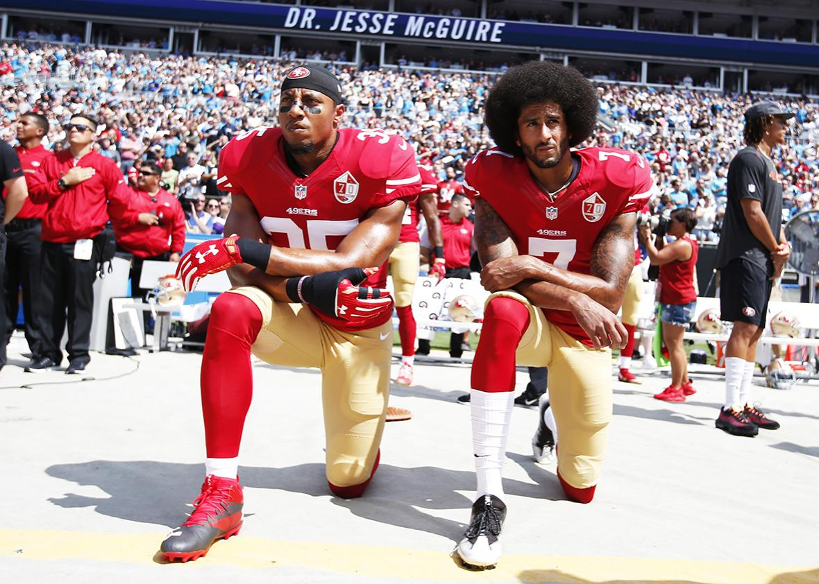 Eric Reid #35 and Colin Kaepernick #7 of the San Francisco 49ers kneel on the sideline, during the anthem, prior to the game against the Carolina Panthers at Bank of America Stadium on September 18, 2016 in Charlotte, North Carolina.