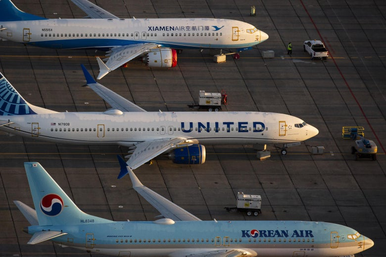 Three Boeing 737 Max airplanes are parked side by side on the tarmac.