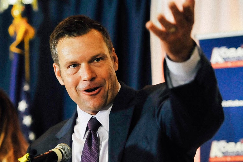 Kobach speaking at a podium, with his left arm raised.