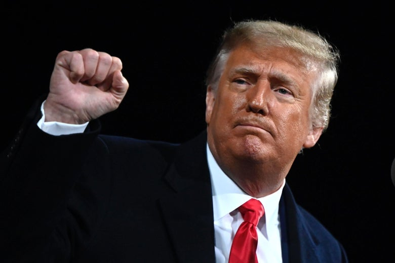 Donald Trump raises his fist as if in solidarity.