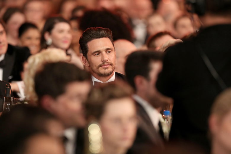 James Franco seated among other guests.