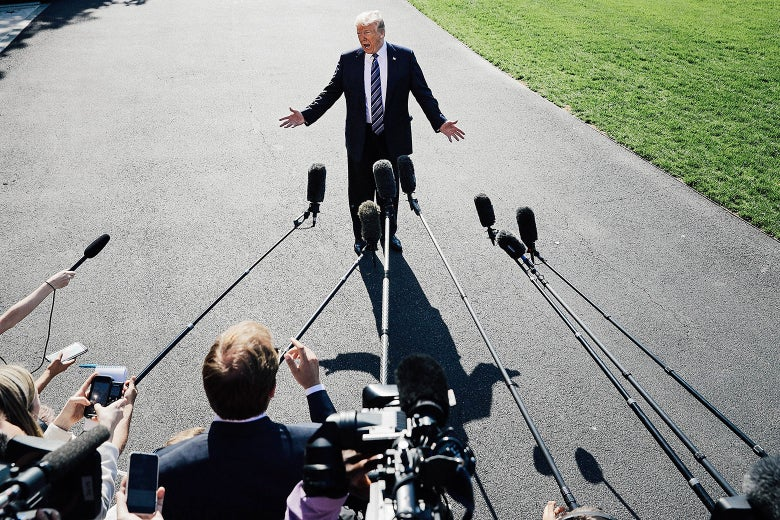 President Donald Trump talks to members of the media before departing the White House on Friday in Washington.