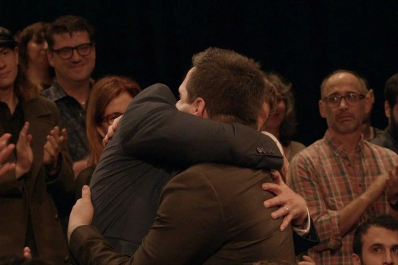 David Wain, stands and applauds as Derek DelGaudio embraces his mom.