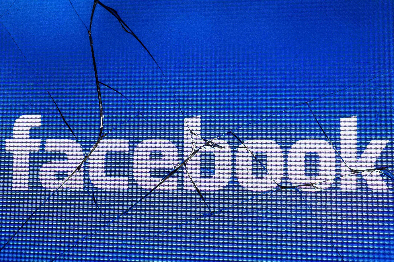 The Facebook logo on a broken screen of a mobile phone.
