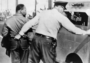 Police officer seizing Dr. Martin Luther King by his pants and leading him to a paddy wagon, after an anti-segregation march in Birmingham, Ala., 1963.