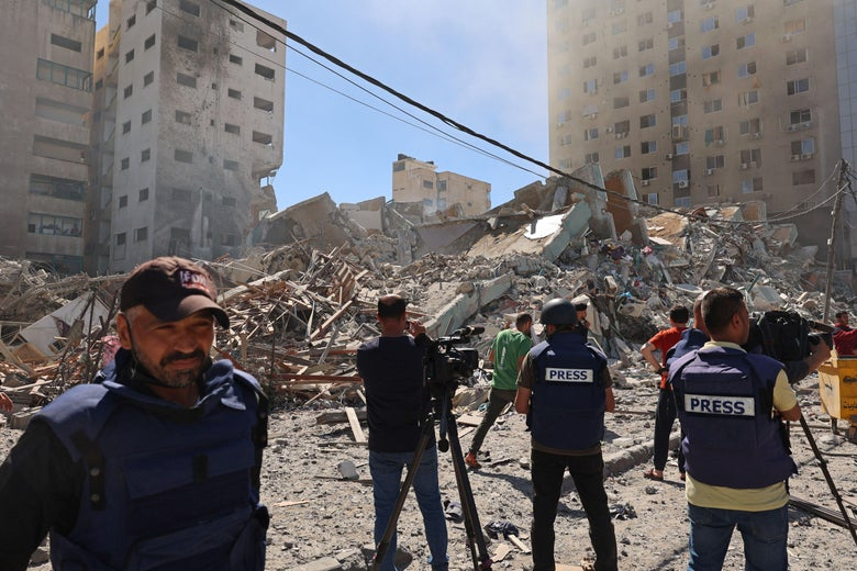 """Several people wearing flak jackets labeled """"press"""" stand in front of a pile of rubble on a clear day"""