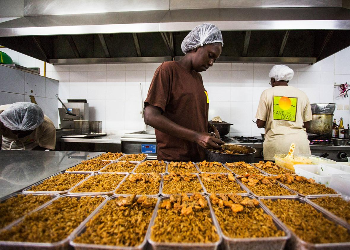 A server scoops fried rice at Saveurs d'Asie, a takeout chain in Senegal run by the son of a Vietnamese immigrant.