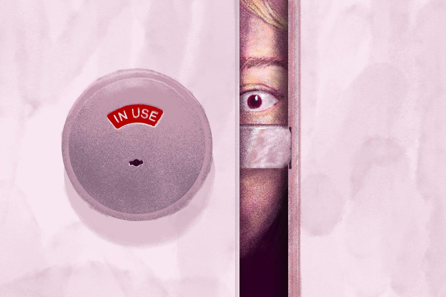 An eye looking through the gap in a bathroom stall door.