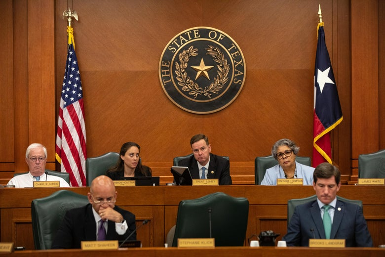 State legislators sit in two raised rows in a committee hearing room in front of American and Texas flags, with the state seal centered on the wall behind them.