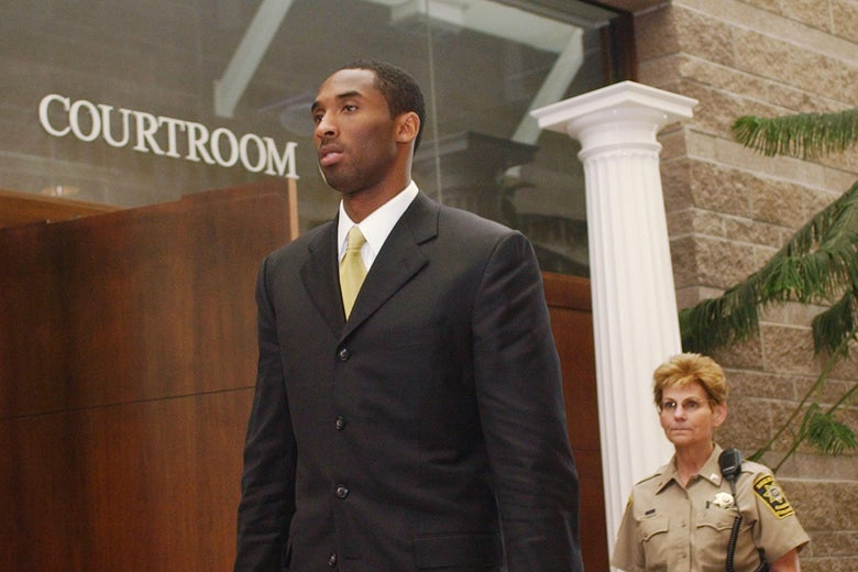 "Kobe Bryant, in a suit, walks under a wall that says ""Courtroom"" as a woman in a law enforcement uniform stands behind him."