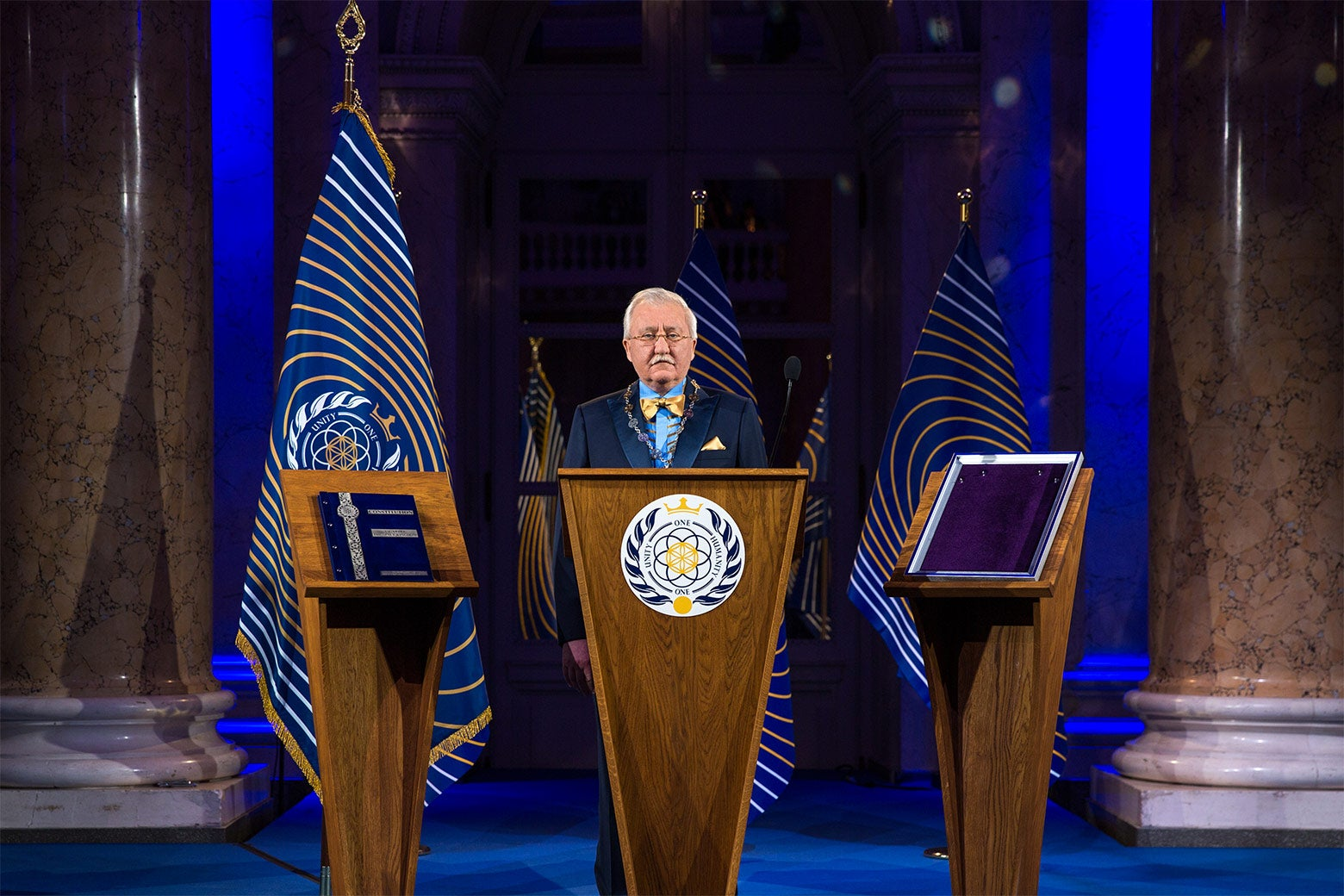 Asgardia President Igor Ashurbeyli stands behind a podium flanked by the flag of Asgardia.