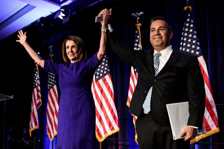Nancy Pelosi and Ben Ray Luján raise their arms at an election-night victory party.