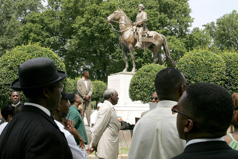 Protesters stand around a statue of Nathan Bedford Forrest.