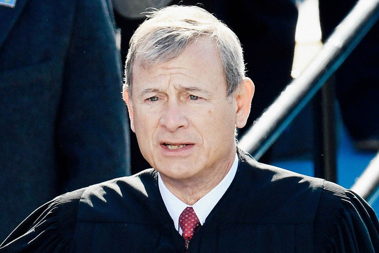 Chief Justice John Roberts stands outside in his robes as he administers the oath of office to Biden