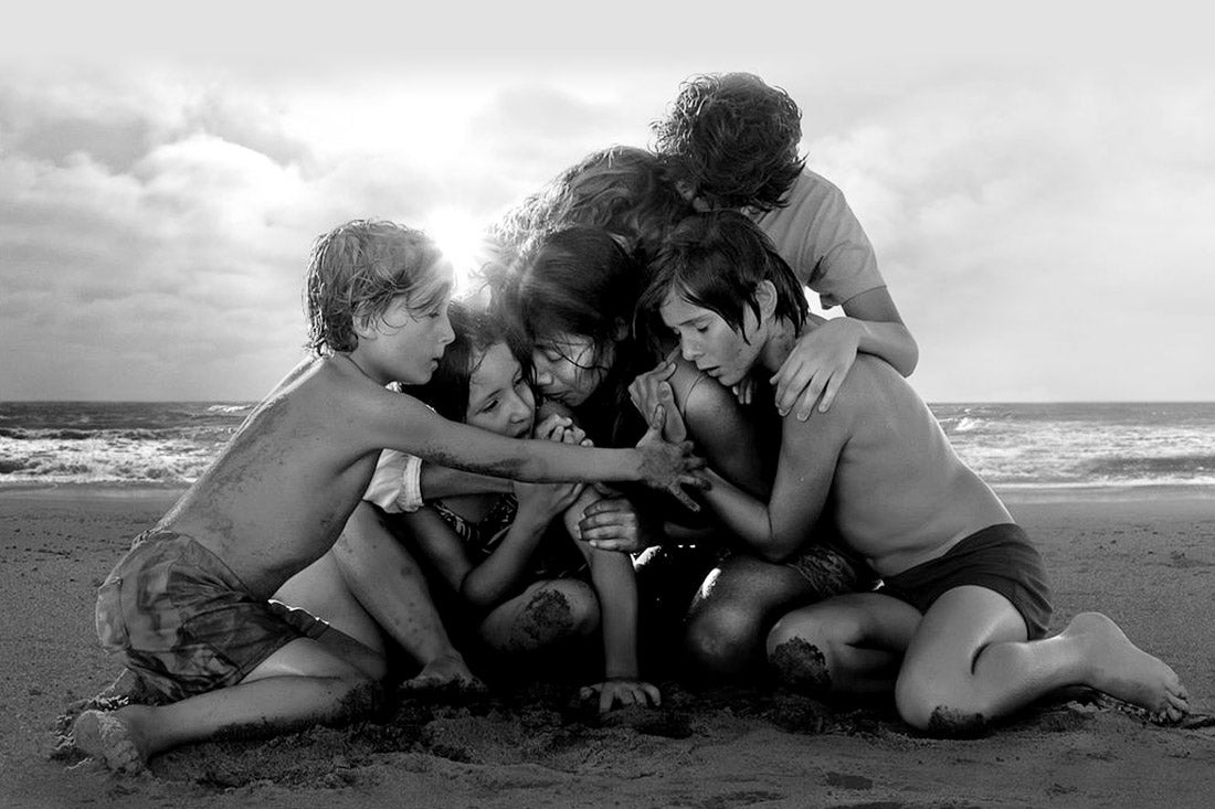 Children huddle around one another and a female adult on the beach.
