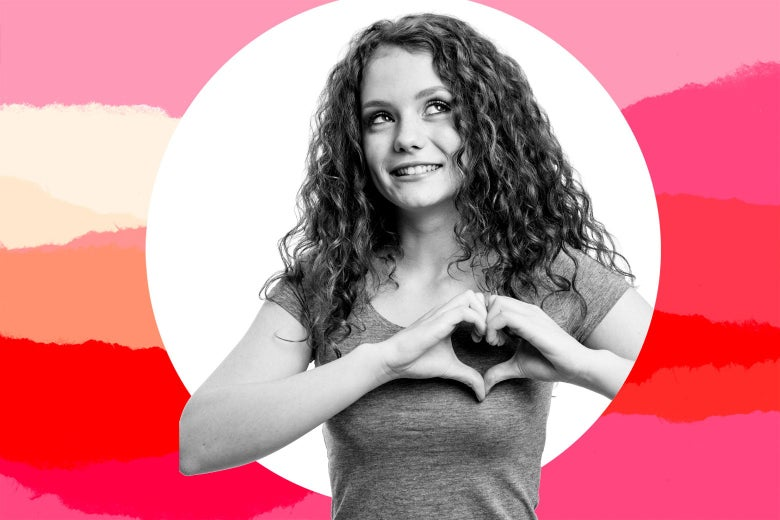 Eight-grade girl making heart hands and looking up.