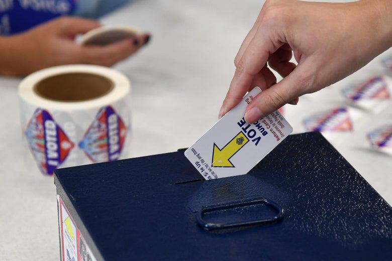 A hand drops a card in a ballot box.
