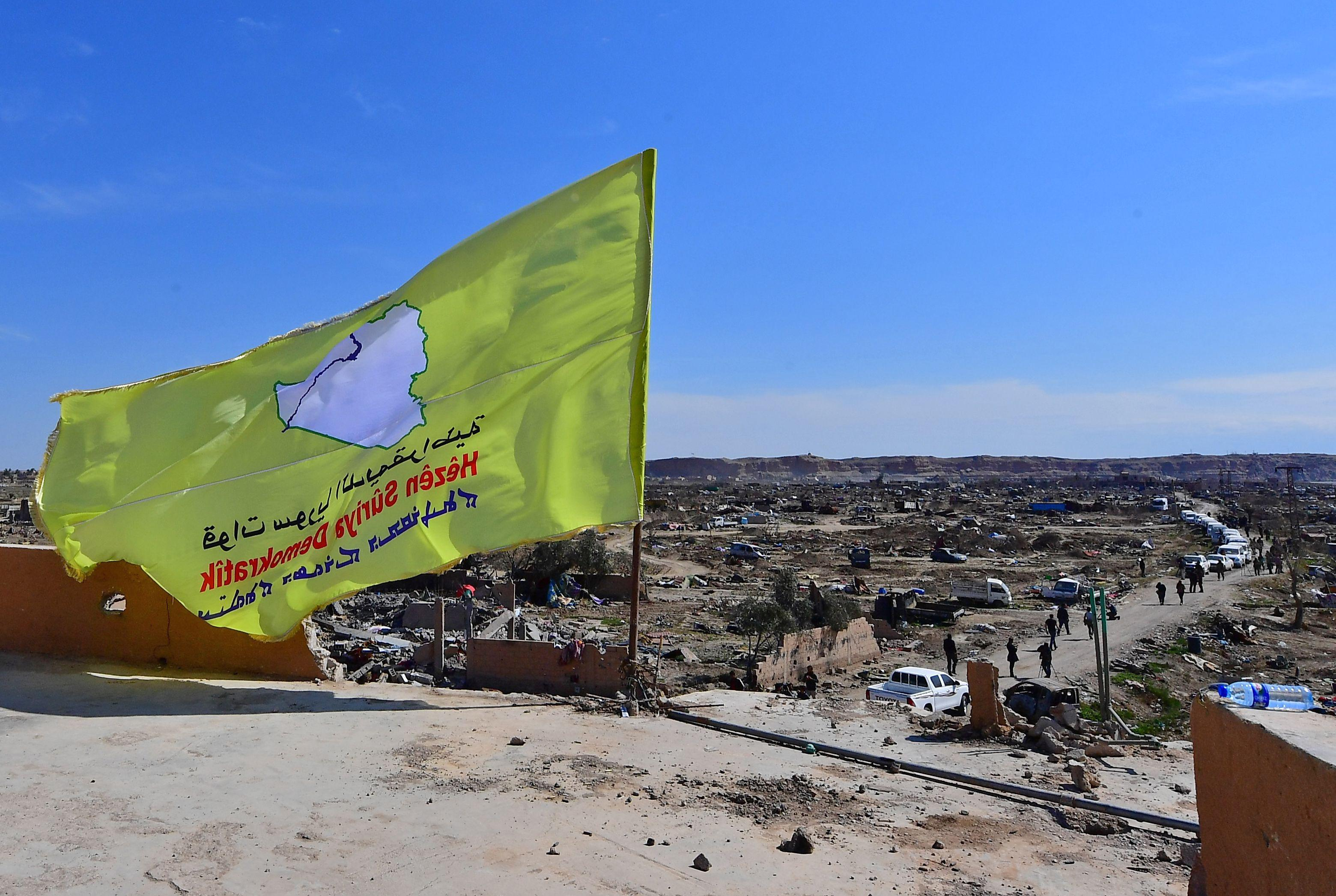 A picture taken on March 23, 2019 shows the US-backed Syrian Democratic Forces' (SDF) flag atop a building in the Islamic State group's last bastion in the eastern Syrian village of Baghuz after defeating the jihadist group.