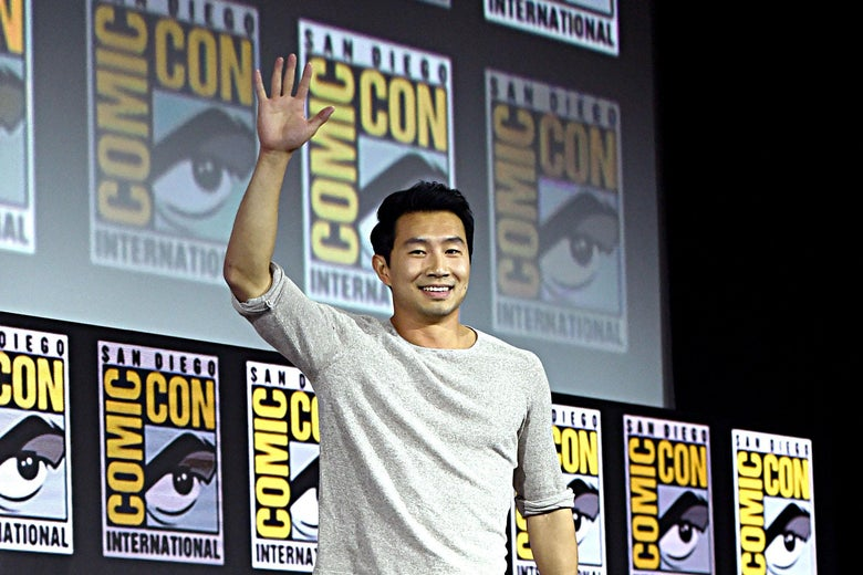 Liu walks across a Comic-Con stage, smiling and waving to the crowd