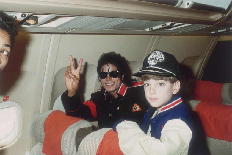 Jackson and Safechuck next to each other on a plane. Jackson is wearing sunglasses, smiling, and making a peace sign at the camera, while Safechuck looks bright-eyed into the camera.