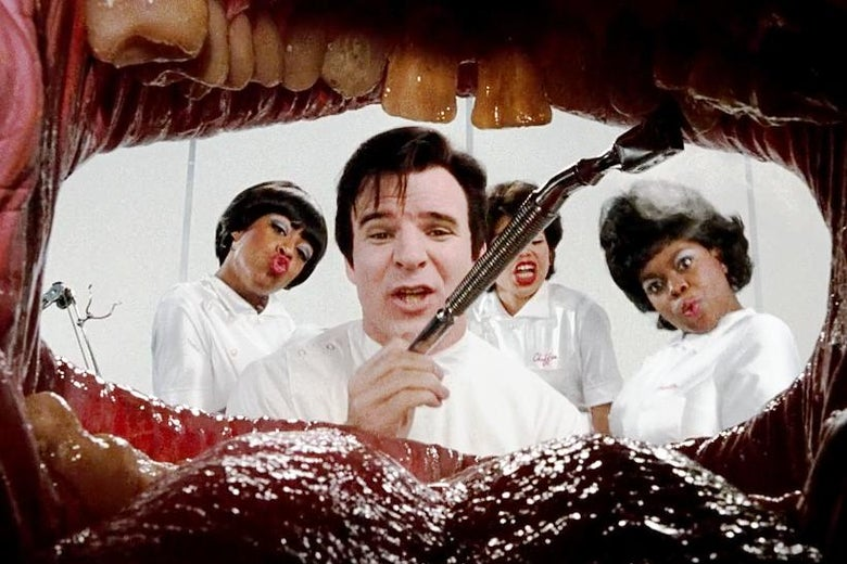 The view from inside a mouth: a dark-haired Steve Martin, dressed as a dentist, framed by a tongue and teeth. Behind him, three women dressed as nurses.