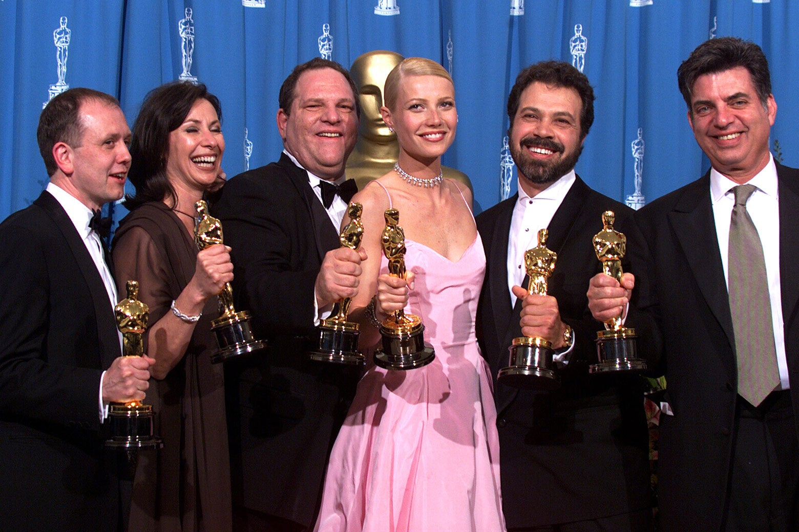 Shakespeare in Love Best Actress winner Gwyneth Paltrow (center) is joined by Harvey Weinstein and others backstage as they celebrated their win of Best Picture at the Academy Awards in Hollywood, California, on March 21, 1999