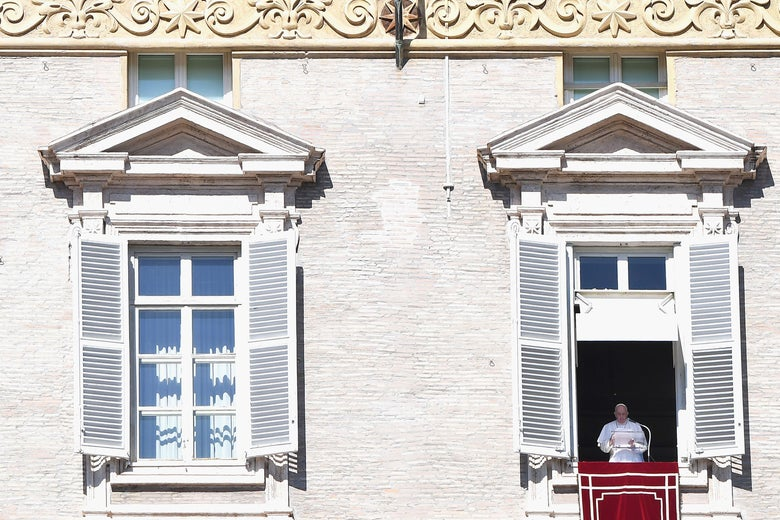 Pope Francis speaks at a lectern from a window overlooking St. Peter's Square