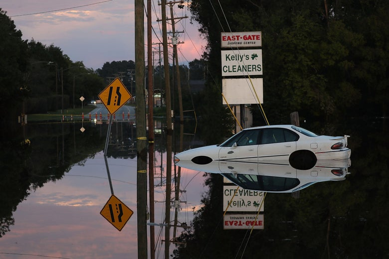A car is partially submerged in floodwater as the sun sets.