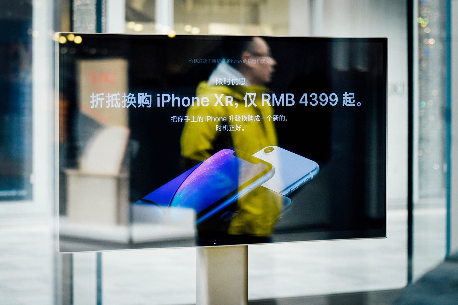 A man is reflected on a screen showing the iPhone XR at an Apple store in Beijing.