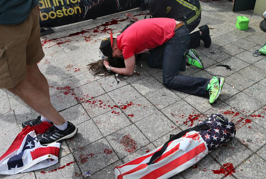 A man comforts a victim on the sidewalk at the scene of the first explosion near the finish line of the 117th Boston Marathon.