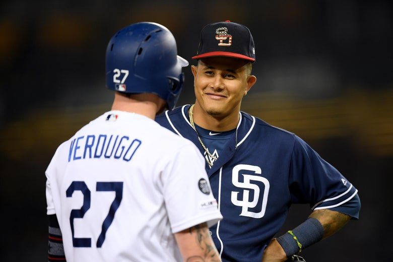 Manny Machado #13 of the San Diego Padres smiles at Alex Verdugo #27 of the Los Angeles Dodgers at third base during the sixth inning at Dodger Stadium on July 5, 2019 in Los Angeles, California.